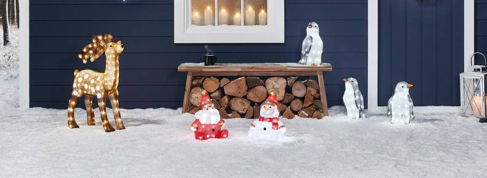 A display of Christmas figures set up outside a blue cabin