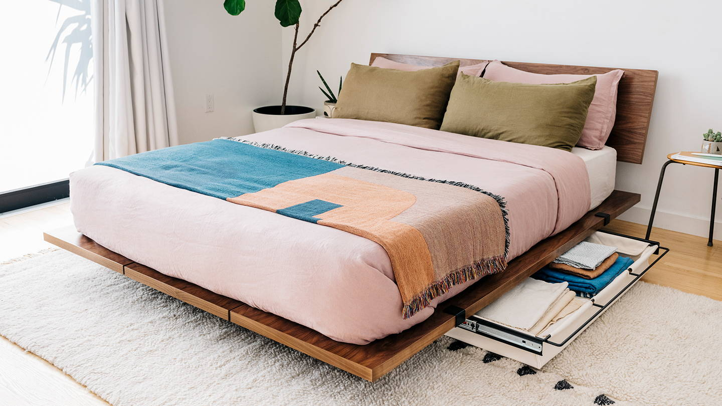 Pastel linens cleanly made on a walnut Floyd bed