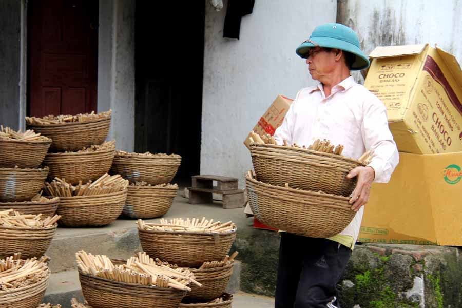 Man moving bamboo straws in baskets