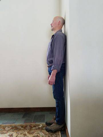 man standing against the wall to assess posture