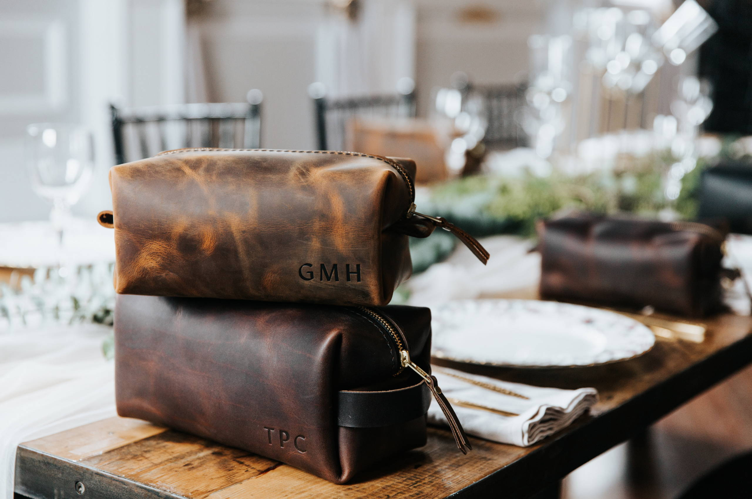 a stack of 2 brown handmade leather dopp kit by portland leather goods on a dinner table