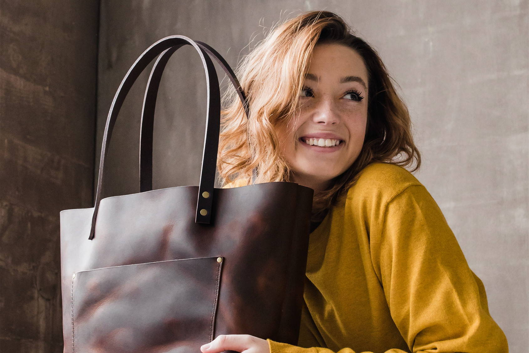 smiling woman holding handmade leather tote bag by portland leather goods