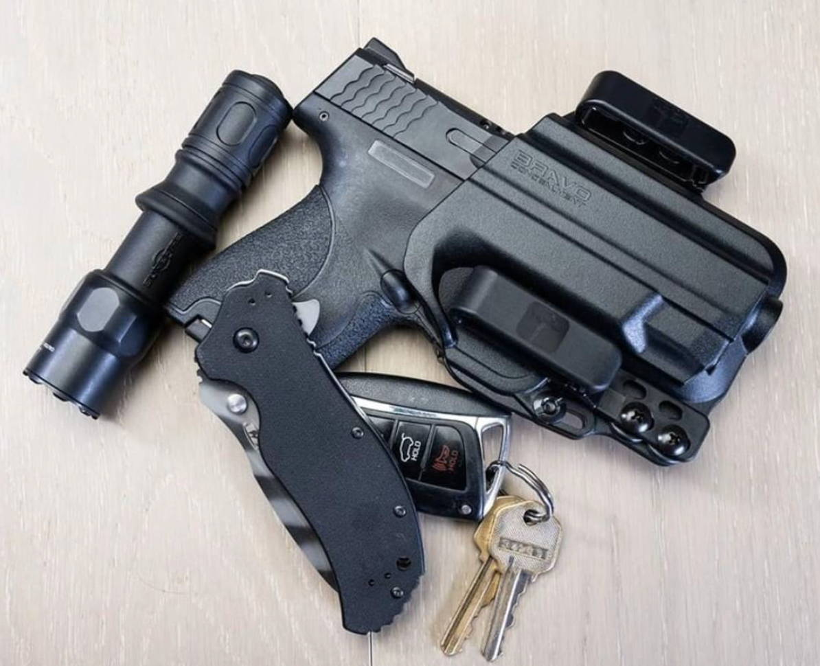 Smith & Wesson M&P Shield holster besides Swiss knife and sight