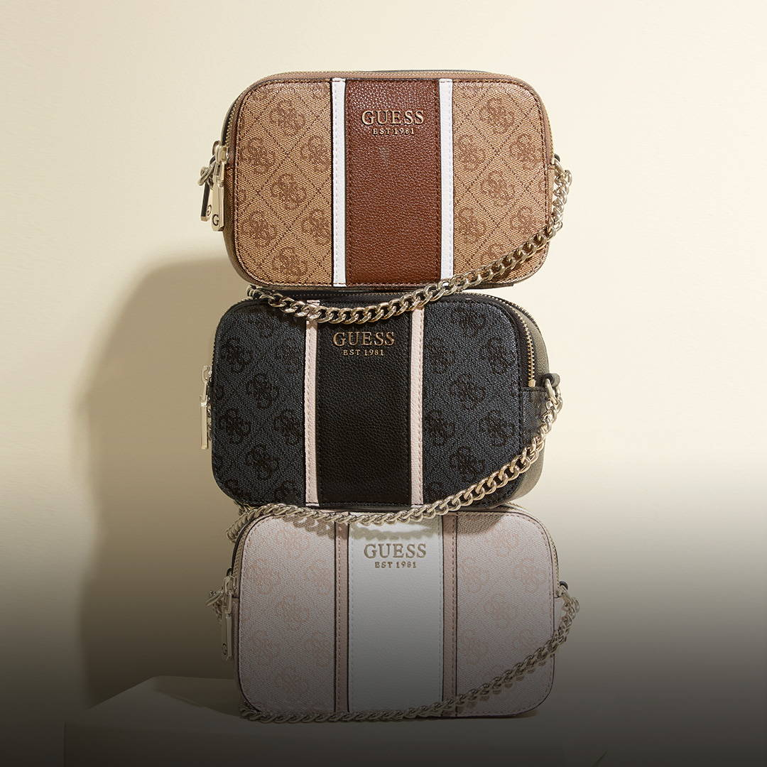 a stack of 3 GUESS small handbags with Guess logo's and gold tone chains