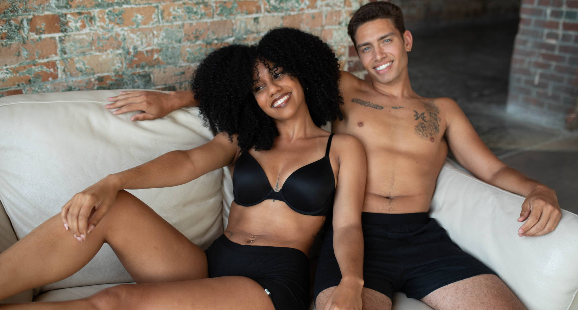 A man and woman cuddle on a couch in WAMA hemp underwear while we discuss why girls wear boxers.