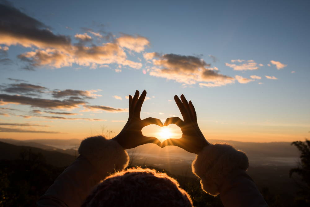 Person Making Heart Sign With The Sun