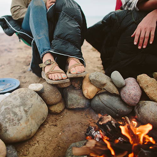 Couple sitting by fire while camping on the beach using a Rumpl blanket