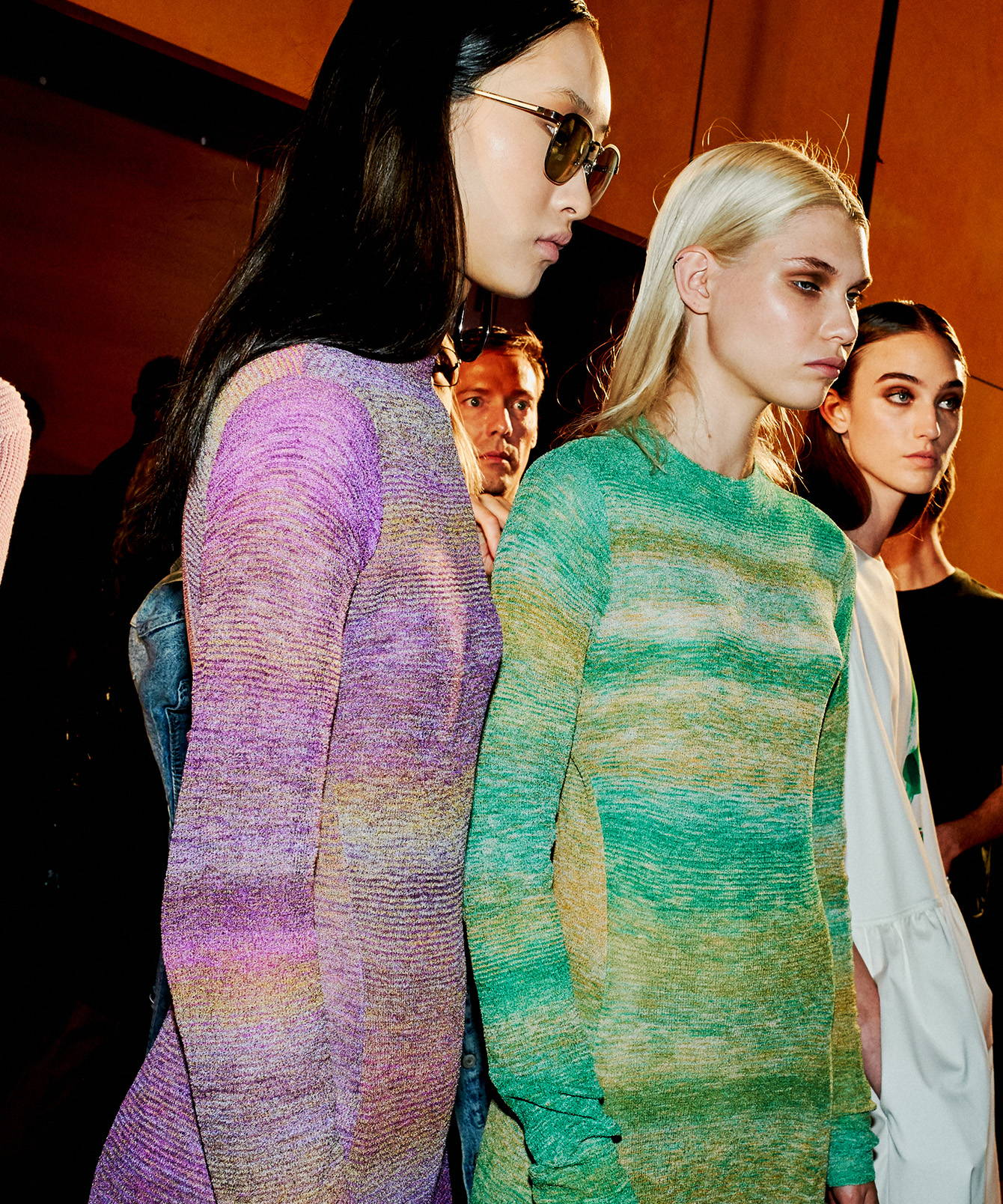 Image of models backstage looking away from the camera. Models are wearing matching knit dresses.
