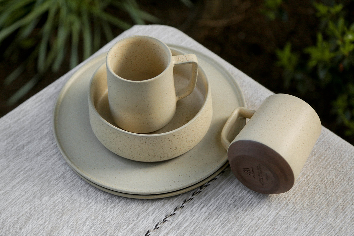 Collection of ceramic tableware on an outside table, including two plates, two mugs and a bowl.