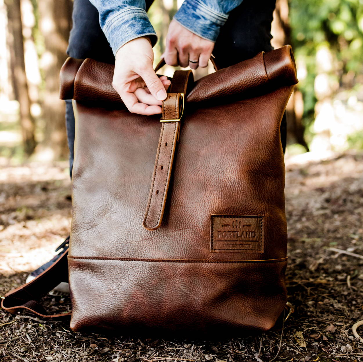 mans hands unbuckling rolltop leather backpack in a forest setting