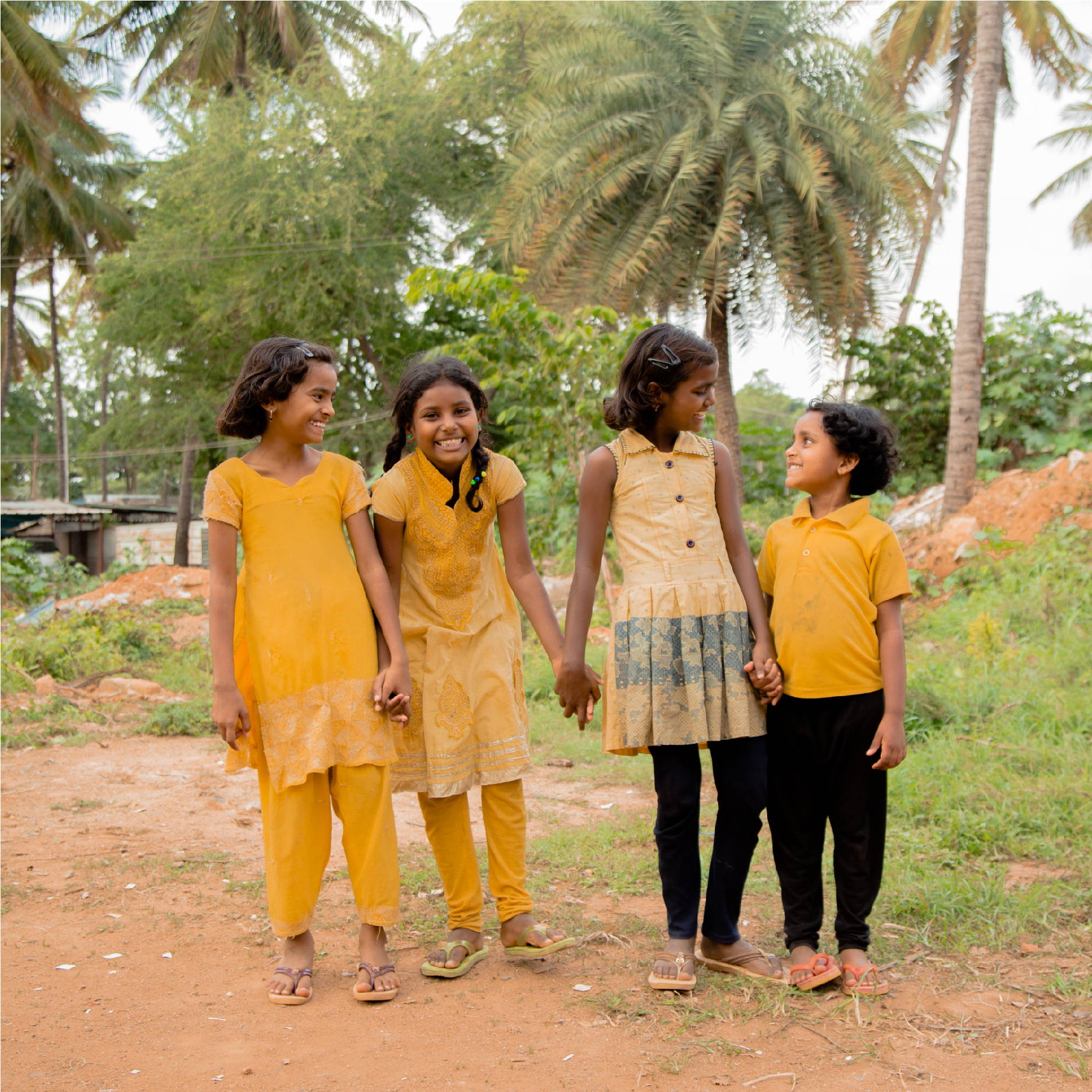 3 young Indian girls, hold hands while smiling, laughing, and looking at each other. They are all wearing yellow dresses.
