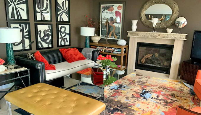 living room with black couch and yellow ottoman on colorful abstract rug in front of beige fireplace