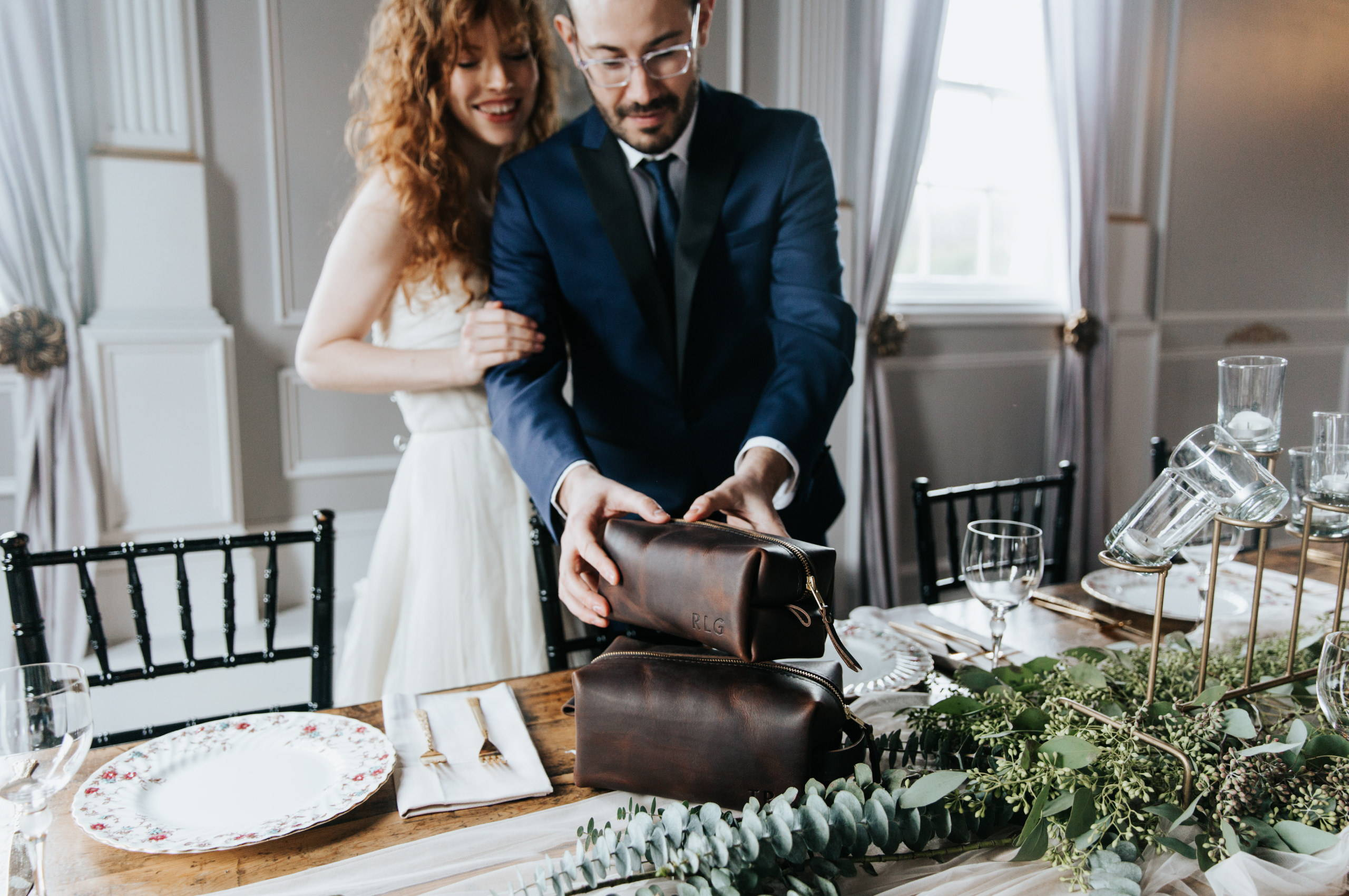 a bride and groom stacking handmade leather dopp kits onto a well decorated dinner table