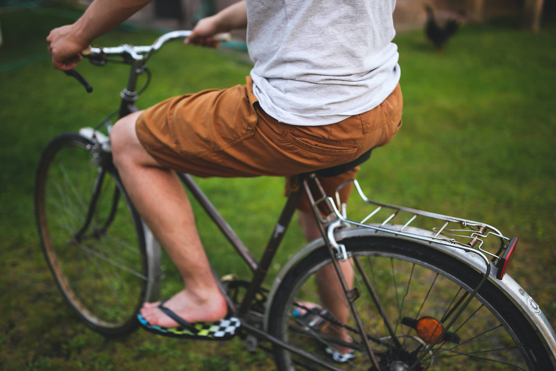 A man wearing hemp shorts rides a bicycle.