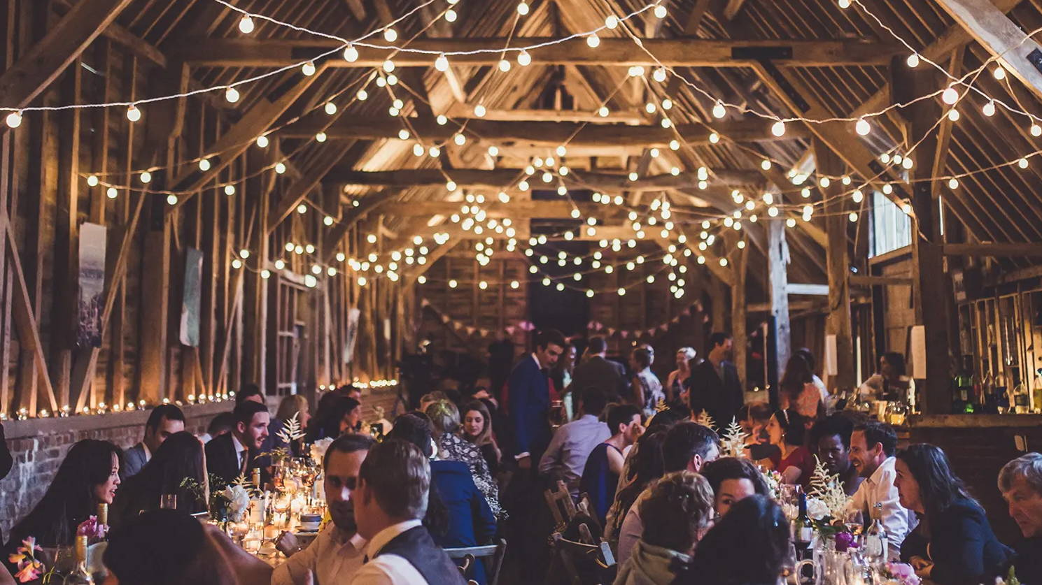 Wedding reception with drop bulb string lights displayed from ceiling