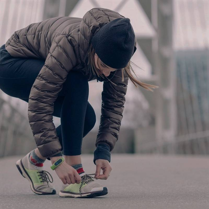 A lady lacing up before for she goes for a run in the city