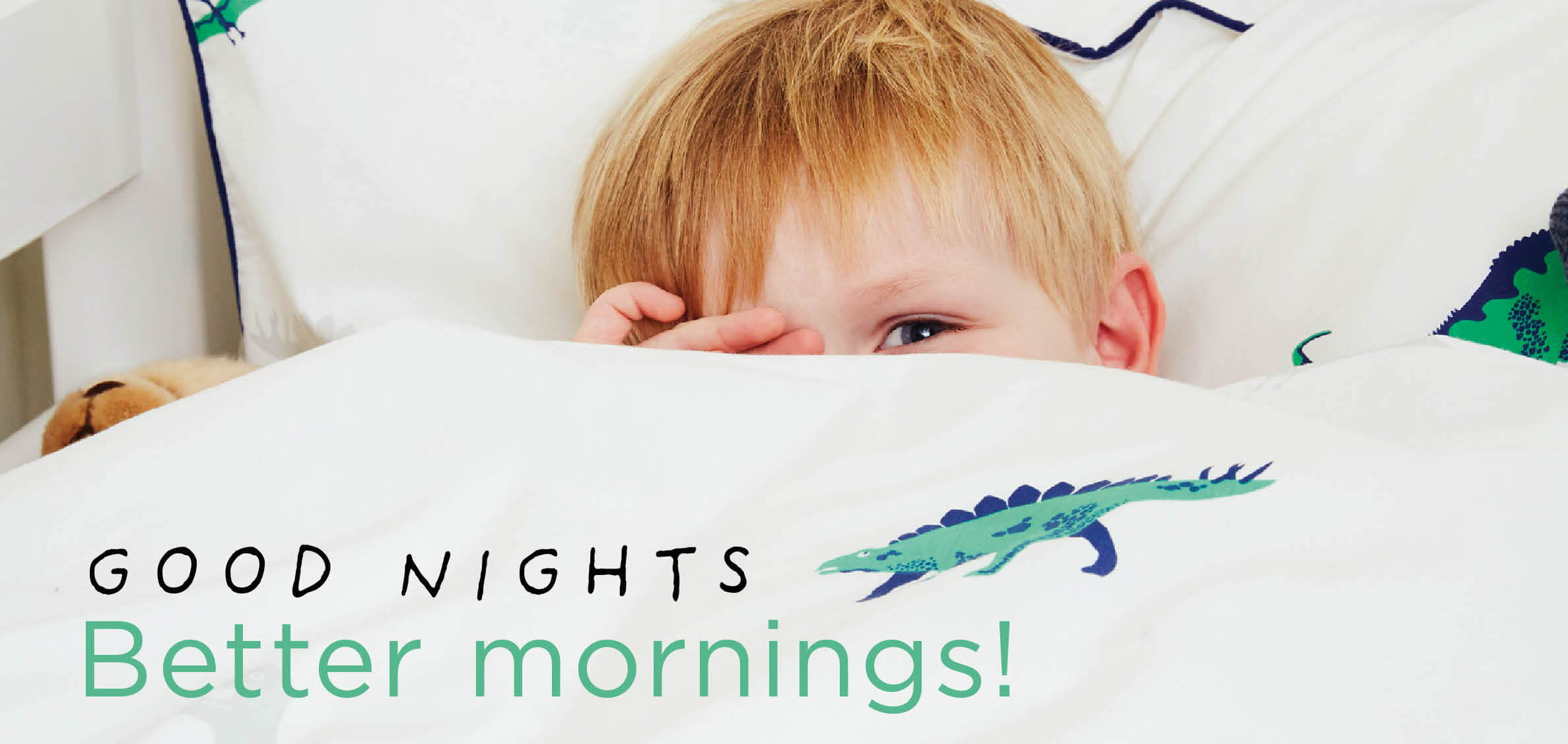 Young boy with dinosaur bedding