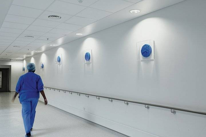 A doctor nurse walking in a hospital next to wall art