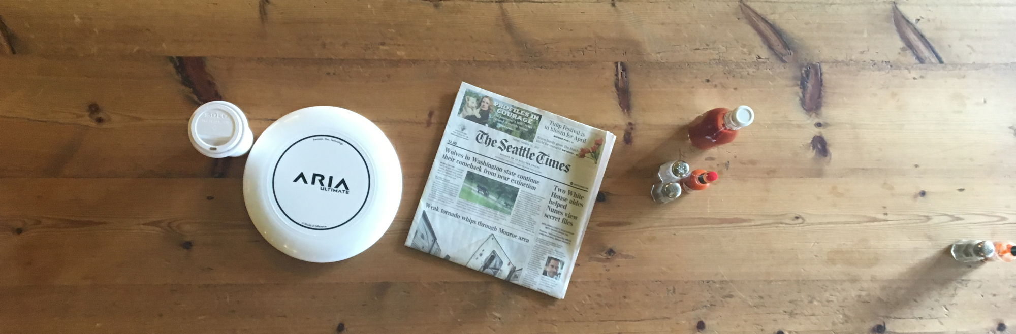 ARIA professional official ultimate flying disc for the sport commonly known as 'ultimate frisbee' aria disc with coffee and newspaper press page (also there's katchup)