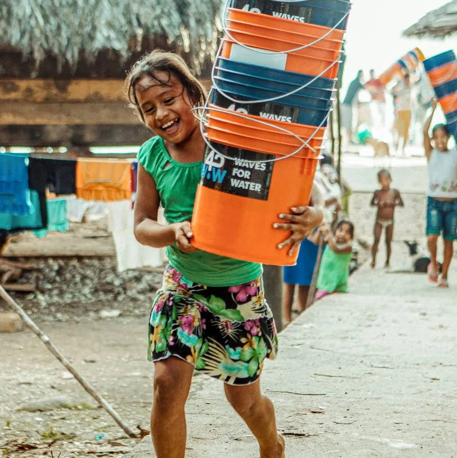 Young happy girl carrying buckets