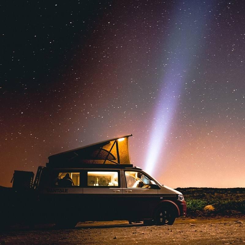 A camper van parked under the stars