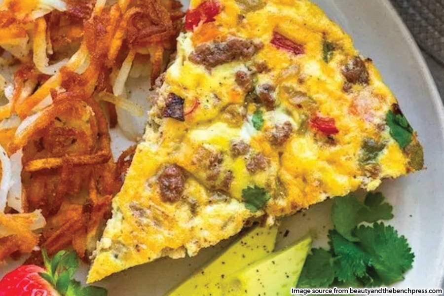 slice of frittata on plate with garnish and side of shredded hashbrowns