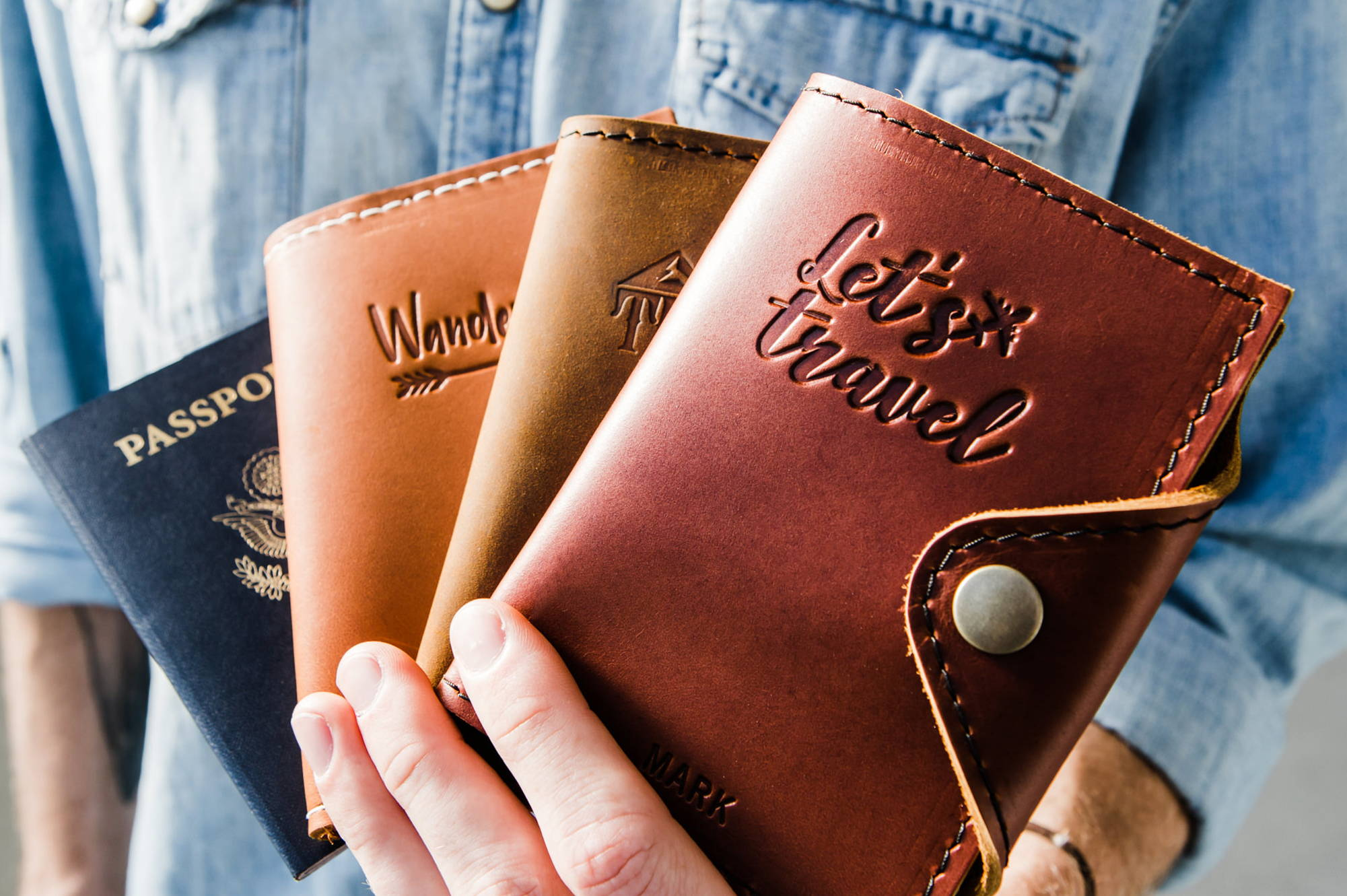 hand holding three colors of handmade leather passport covers