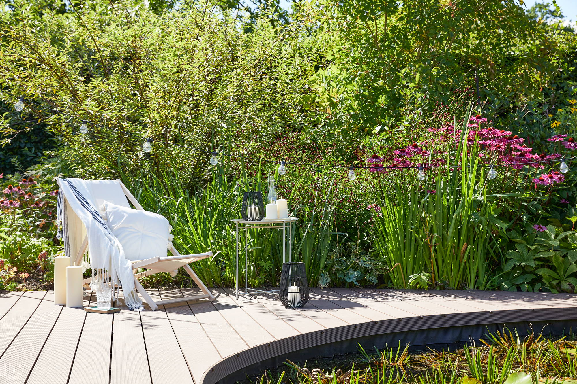 Garden setting with deck chair, pond and bushes featuring lanterns, LED candles and festoons