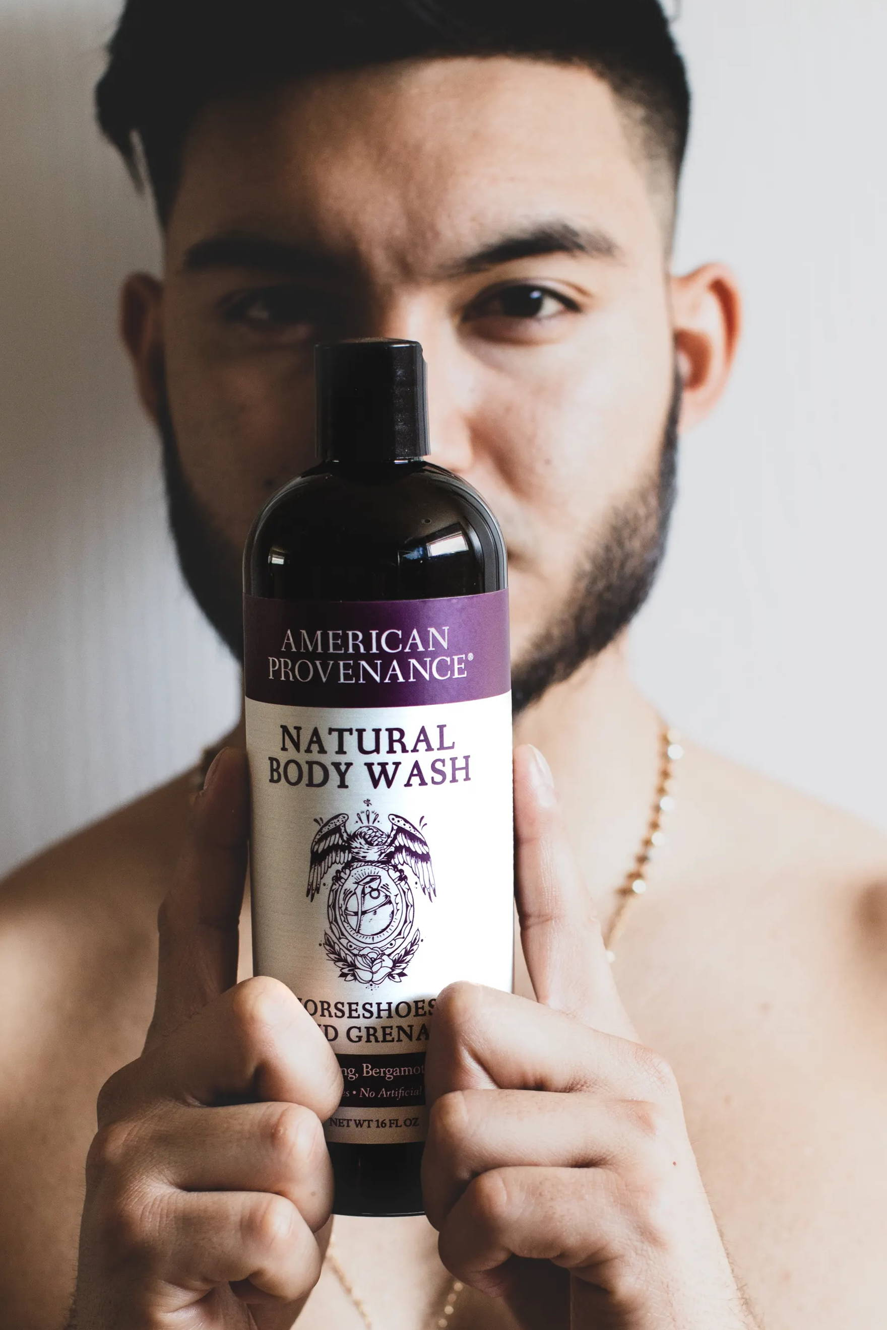 man holding body wash bottle