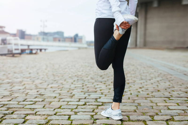 young woman stretching her thigh in before running on cobblestone street.