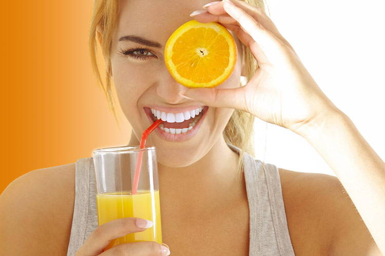 Woman Drinking Orange Juice And Holding An Orange Over Her Eye
