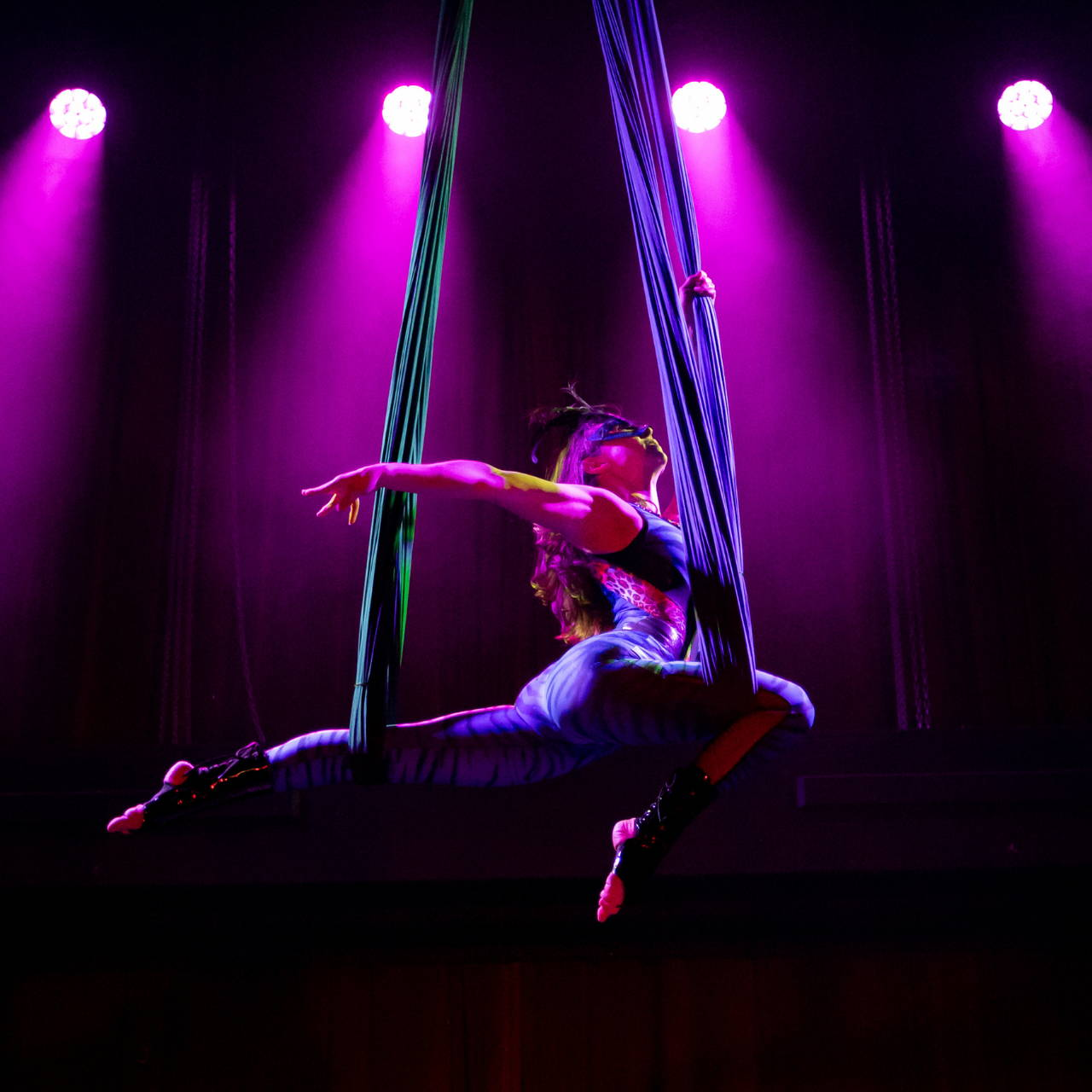 Aerialist performing on silks, wearing a blue mask and leotard on purple backlit background