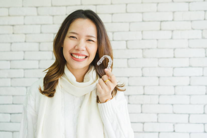 A woman with brown hair and a white sweater smiling and holding up a clear aligner