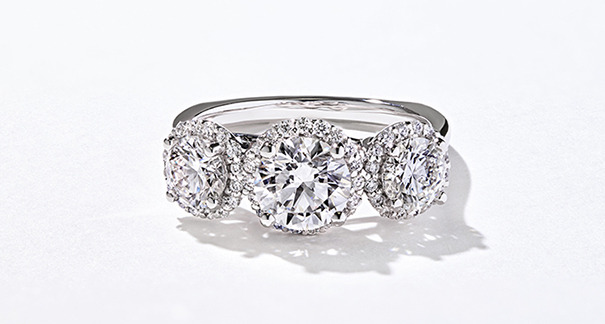 Custom diamond three stone ring with a halo of diamonds around each ring