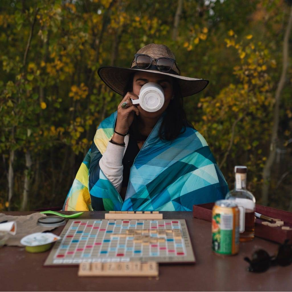 Woman drinking coffee at a table playing scrabble with a Rumpl blanket