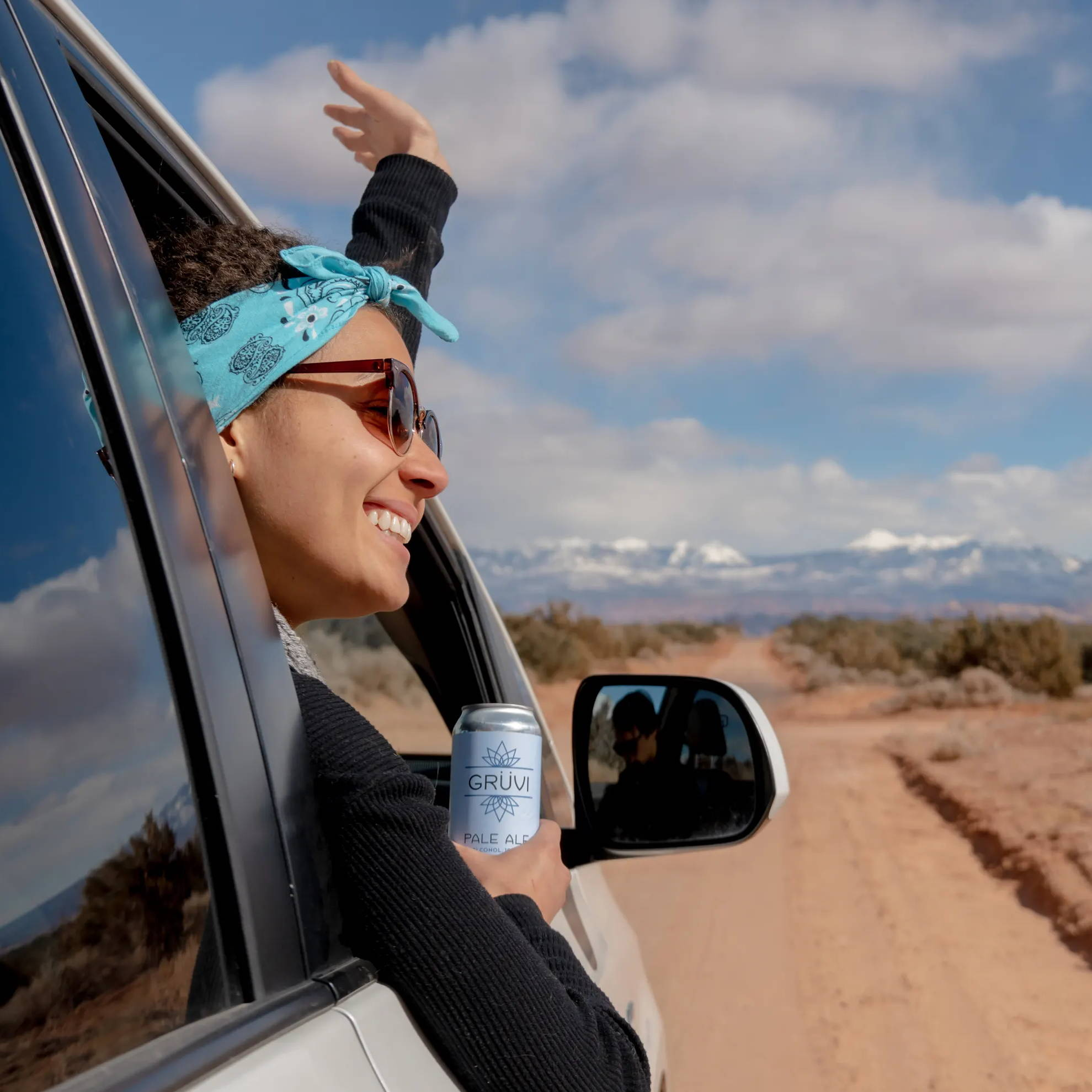 A woman is smiling and leaning out of her car window holding a Grüvi Pale Ale. The car is headed towards the mountains in the background.
