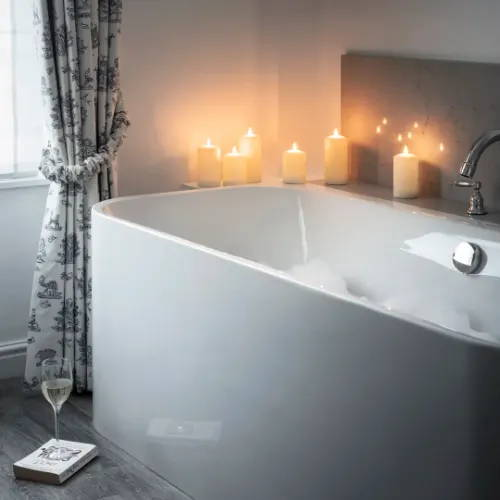 Illuminated candles placed around bubble bath