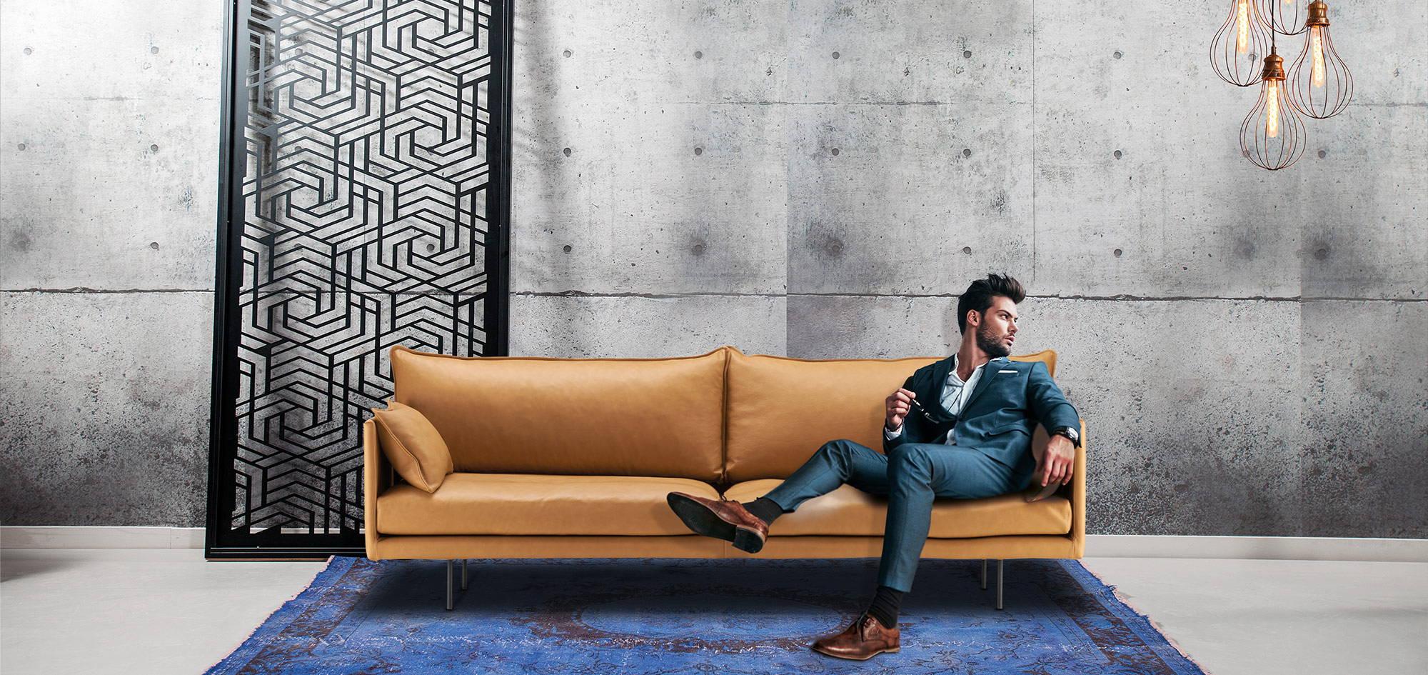 Air-sohva, ruskea nahka, mies istuu sohvalla. HT Collection