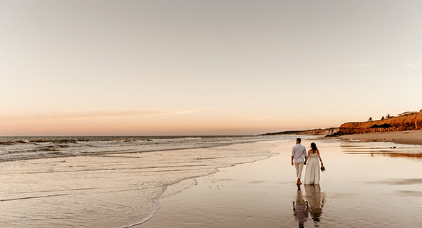 A married couple walking on an Oregon beach during a sunset
