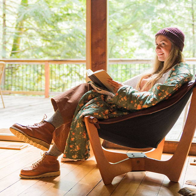 Woman wrapped in a sherpa blanket reading her book in a cabin