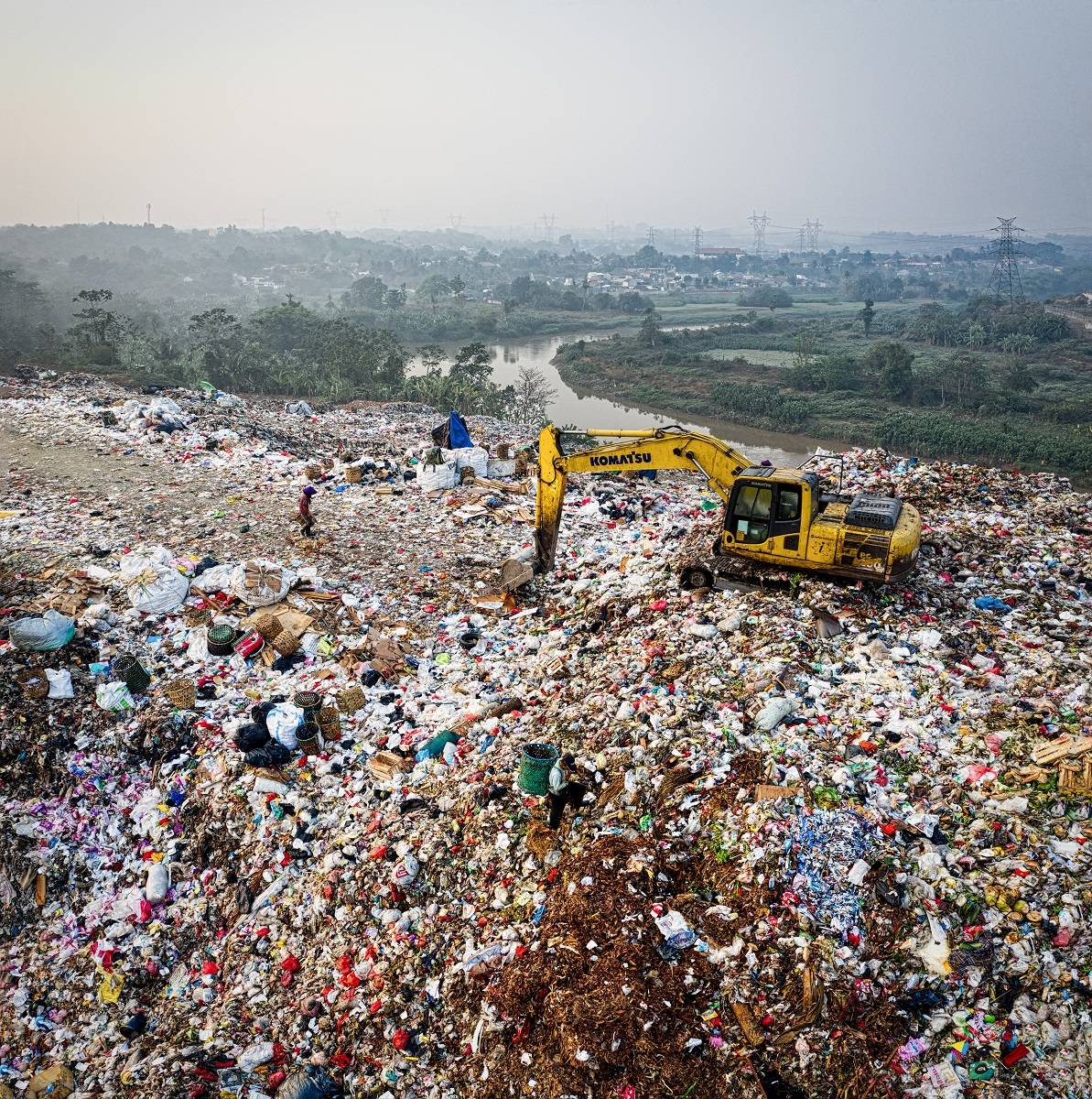 An excavator moving waste at a landfill site