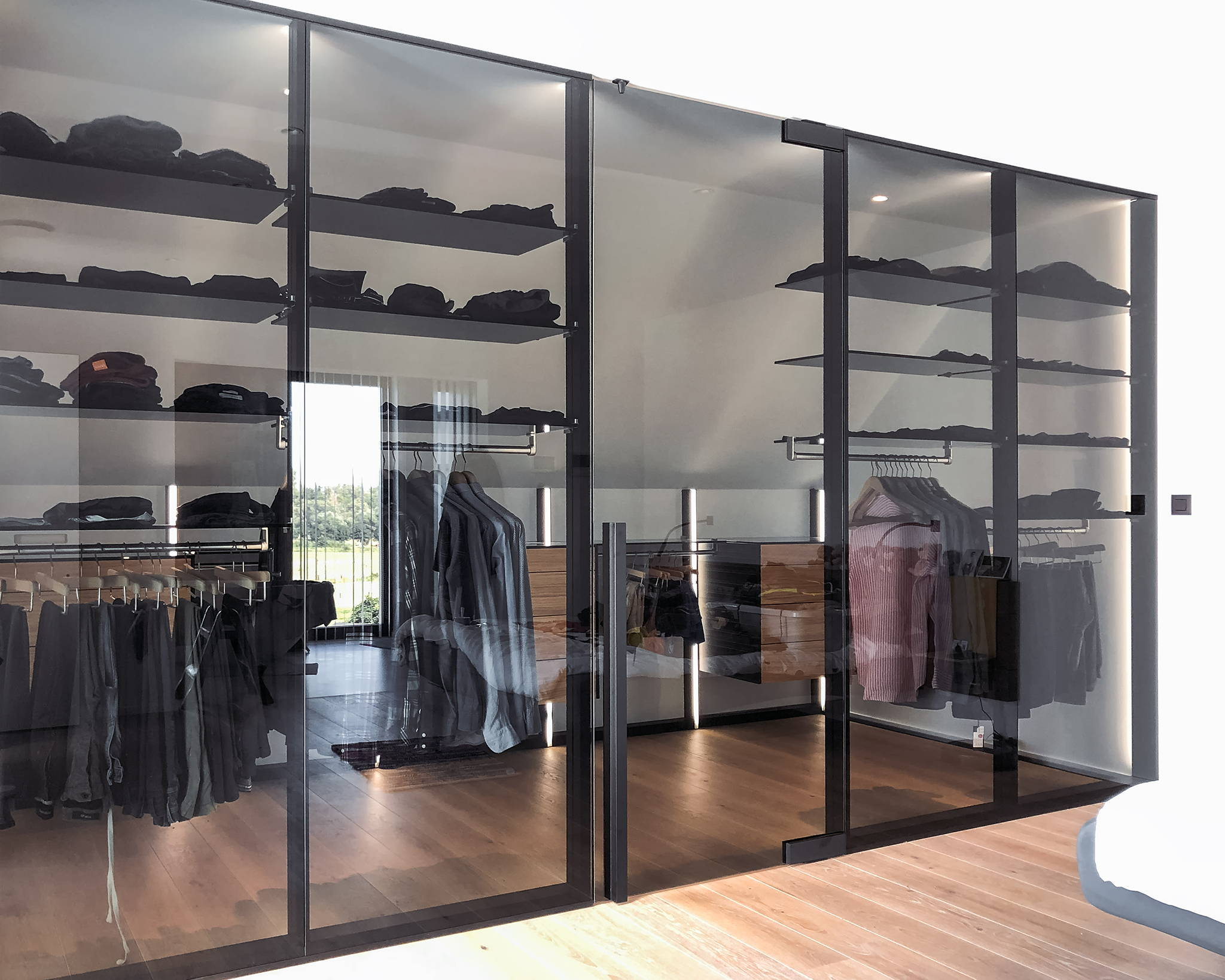 Luxury walk-in closet with a glass entry door