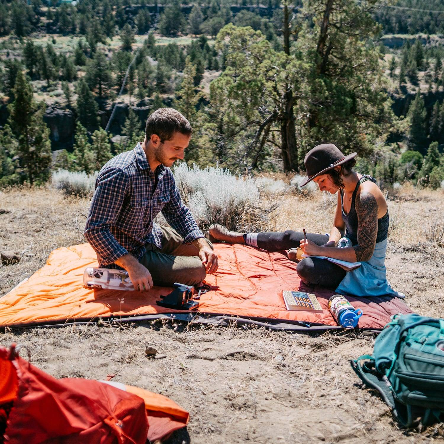 Couple sitting on picnic blanket outdoors