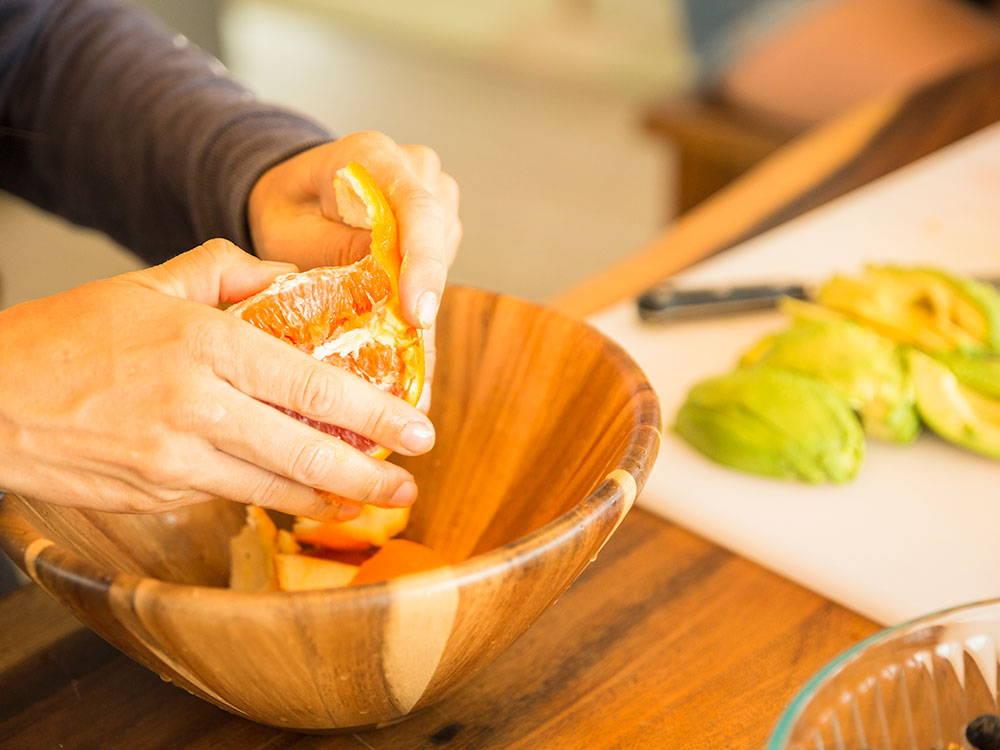 peeling an orange into a bowl