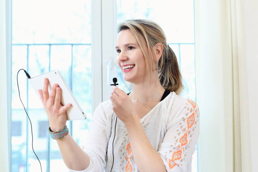 woman using wired lavalier microphone on ipad