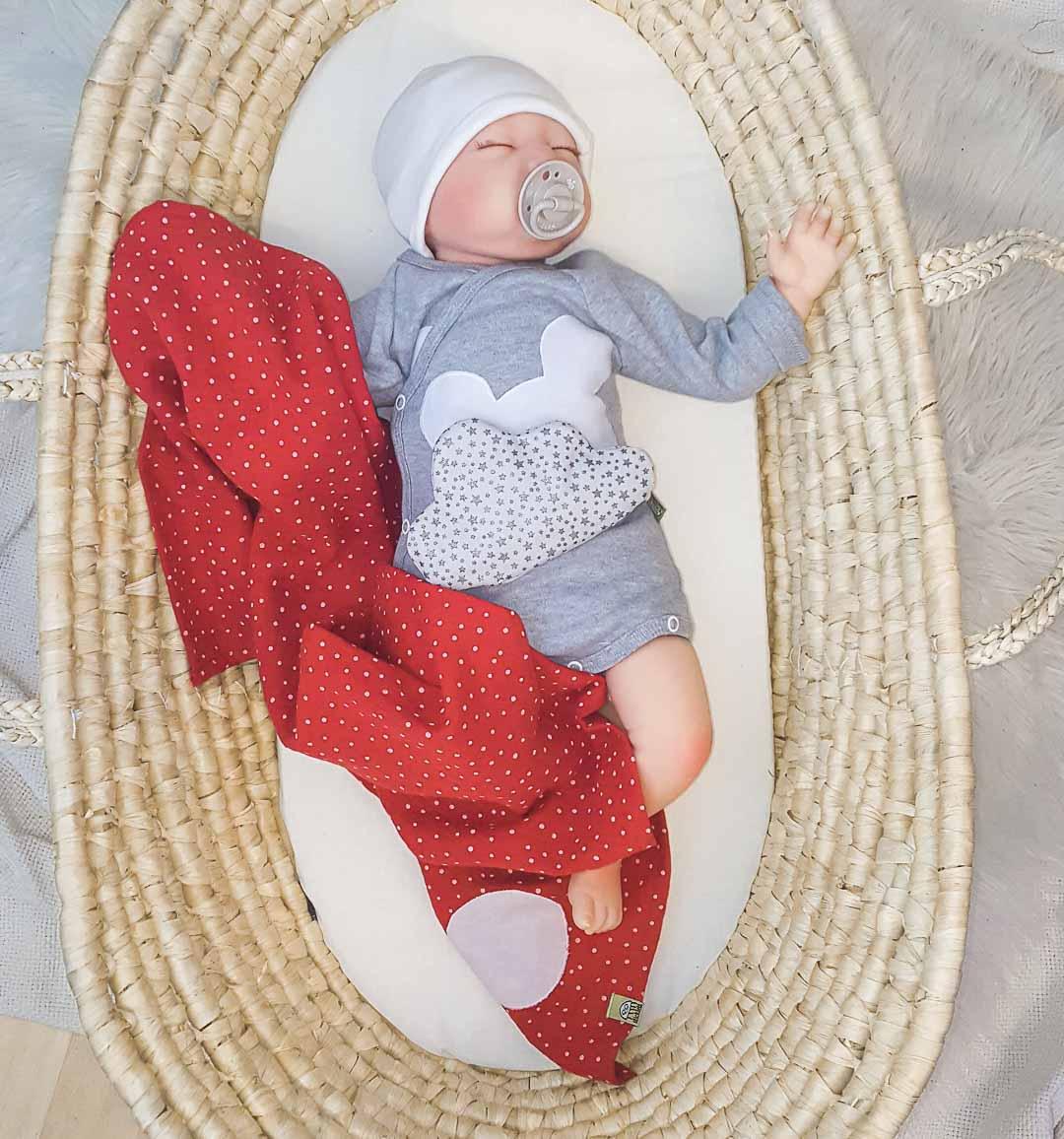 Baby mit Wickelbody, selbsthaftendem Wohl-Fühl-Wärmepatch und Musselin-Tuch in rot und grau