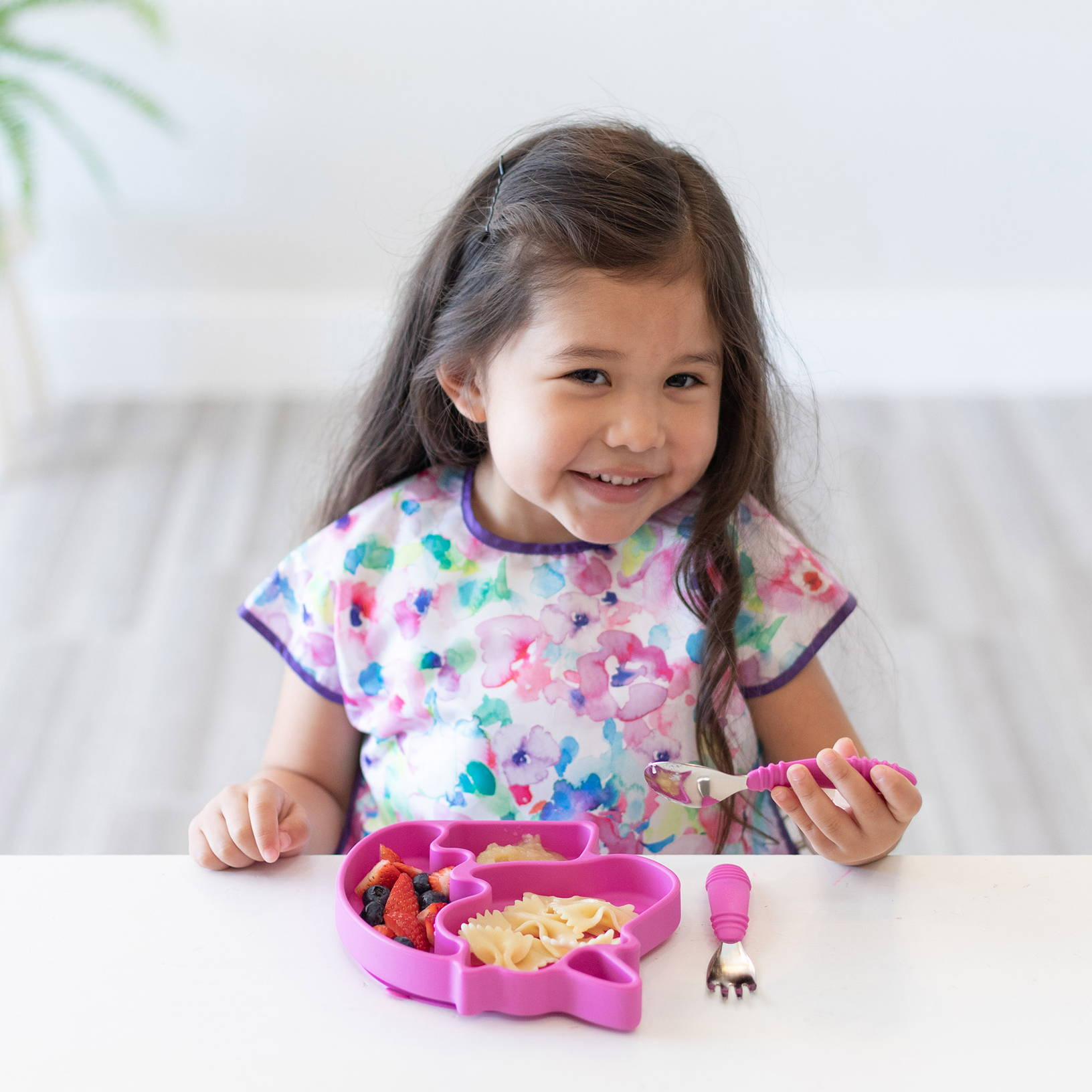 kid eating from unicorn plate with pink utensils
