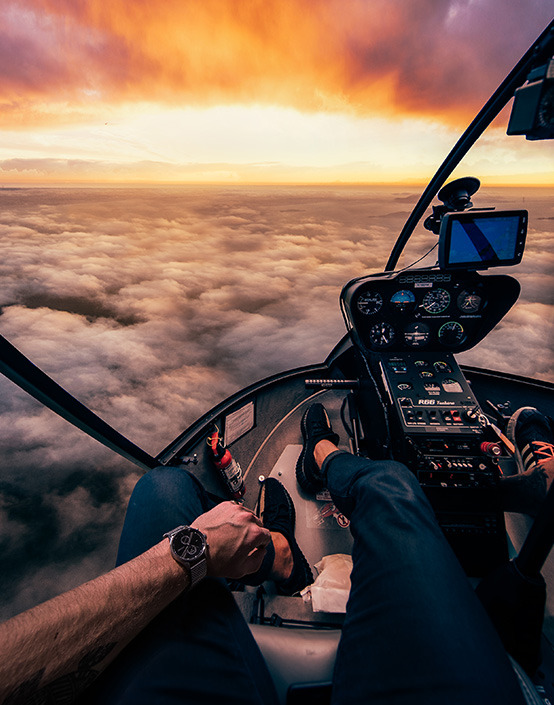 first person view of man in helicopter cockpit above clouds