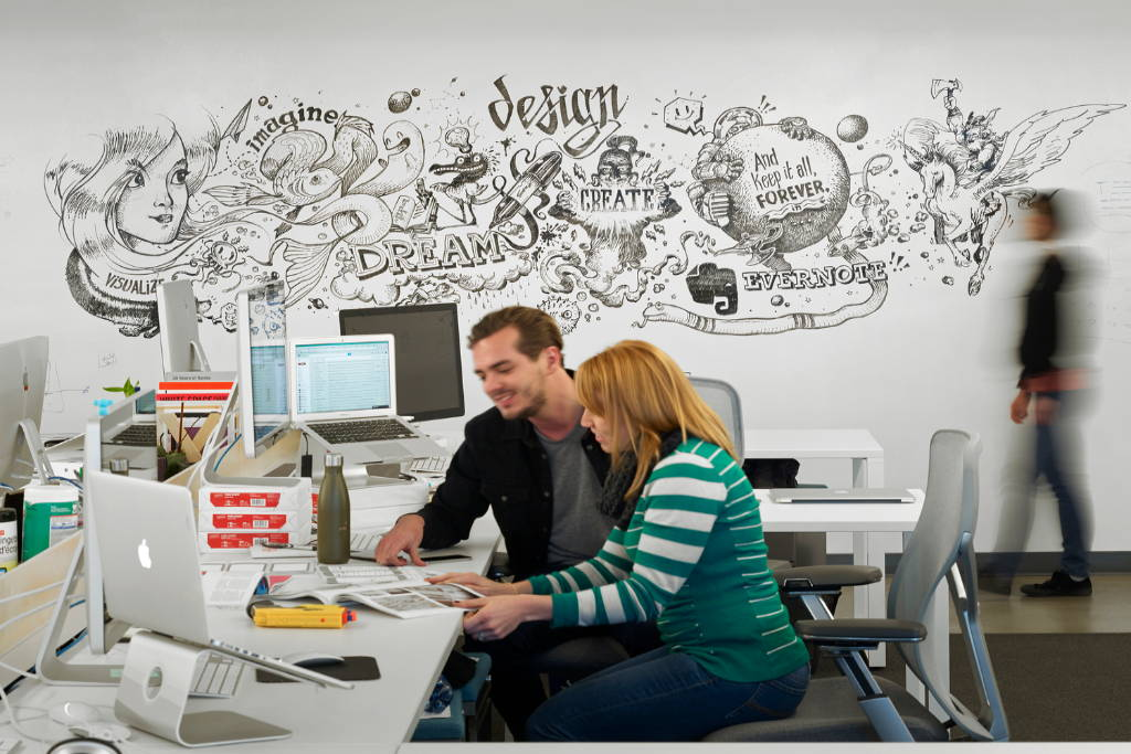 Two employees working together in front of an IdeaPaint Dry Erase wall mural.