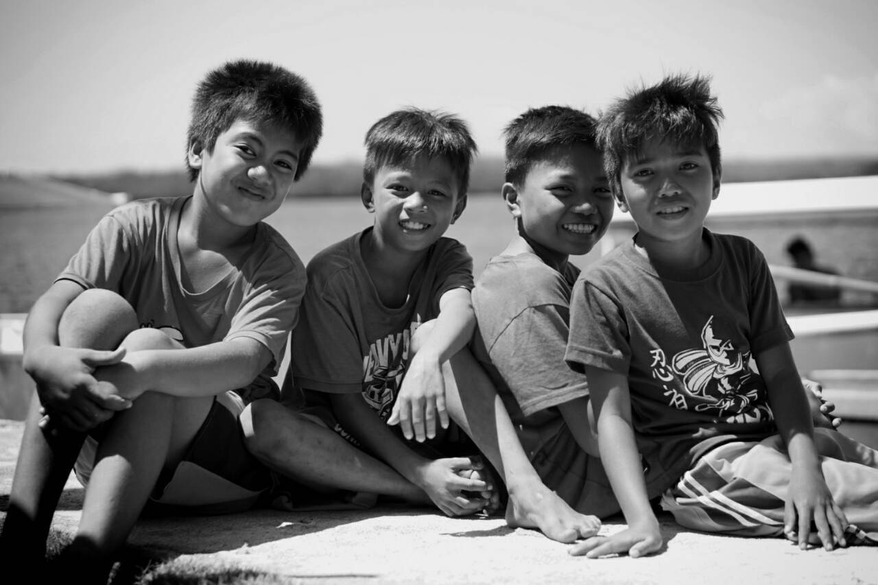 four young boys smiling together at the camera